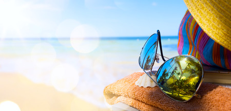 Photo pour Straw hat, bag and sun glasses  on a tropical beach - image libre de droit