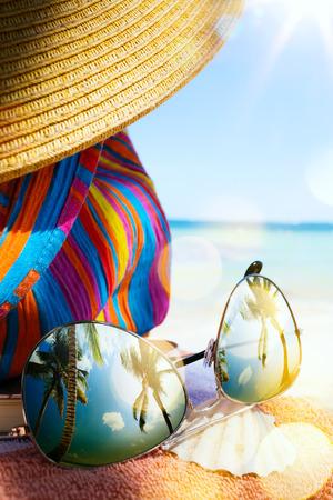 Photo pour Straw hat, bag and sun glasses  on a tropical beach - image libre de droit