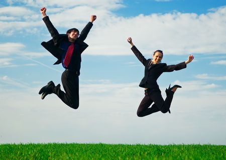 two happy colleagues jumping at the green field