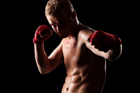 young caucasian fighter boxing over black background