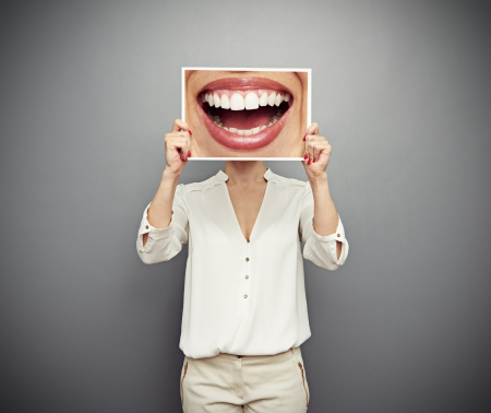 Photo for woman holding picture with big smile. concept photo over dark background - Royalty Free Image