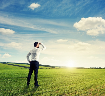 Photo pour back view of businessman on green field - image libre de droit