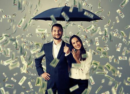 Foto de smiley successful couple with umbrella standing under money rain - Imagen libre de derechos