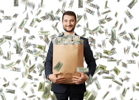 Photo pour smiley young businessman holding paper bag with money under dollar's rain - image libre de droit