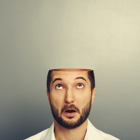 Photo pour surprised man looking up at his open empty head. photo over grey background - image libre de droit