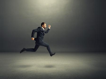 Foto de happy businessman in formal wear running over dark background - Imagen libre de derechos