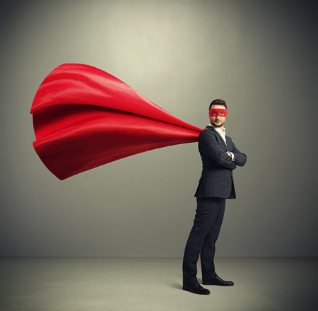 Photo pour serious businessman dressed as a superhero in red mask and cloak over dark grey background - image libre de droit