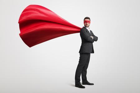 Foto de serious businessman dressed as a superhero in red mask and cloak over light grey background - Imagen libre de derechos