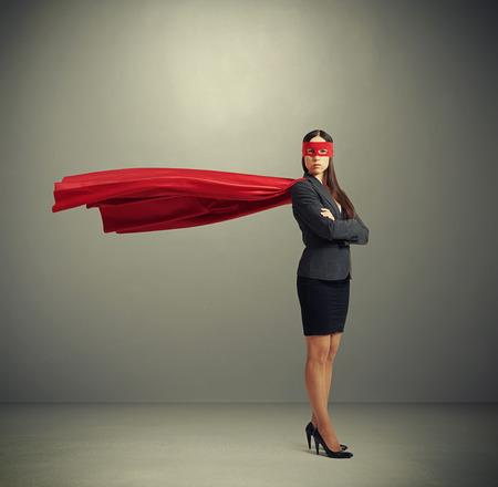 Foto de serious businesswoman dressed as a superhero in red mask and cloak over dark grey background - Imagen libre de derechos
