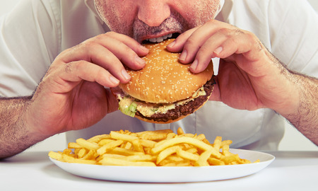 Photo pour close up photo of man eating burger and french fries - image libre de droit
