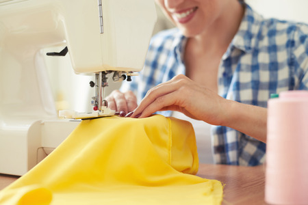 Foto per smiley woman sewing on sewing-machine. focus on sewing-machine - Immagine Royalty Free