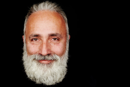 Foto de close-up portrait of smiley bearded man over black background with empty copyspace - Imagen libre de derechos