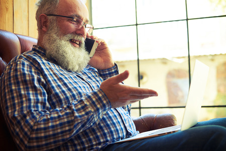 Photo pour smiley senior man sitting on the couch with laptop and talking on the phone at home - image libre de droit