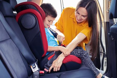 Foto de Wide shot of gorgeous mom helping son sitting in baby seat to fasten seat belt - Imagen libre de derechos