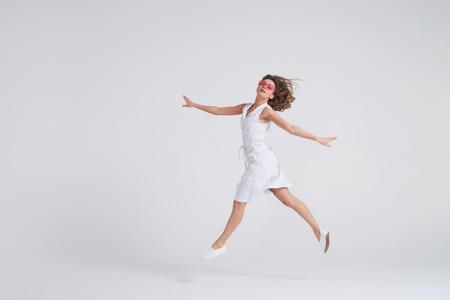 Foto de Full-length shot of cheerful girl jumping in air over white background - Imagen libre de derechos