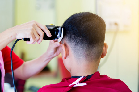 Photo pour Barber shop. hairdresser makes hairstyle to a asian boy with hair clipper and white comb. Fashionable haircut for boys. - image libre de droit
