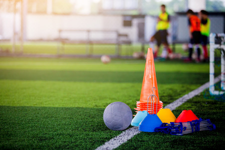 Photo pour Football and soccer training equipment on green artificial turf with blurry player training background. Soccer Academy. - image libre de droit