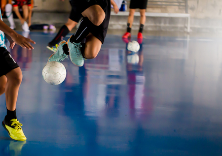 Foto per Futsal player  jump with trap and control the ball for shoot to goal. Soccer players fighting each other by kicking the ball. Indoor soccer sports hall. Football futsal player, ball, futsal floor. - Immagine Royalty Free