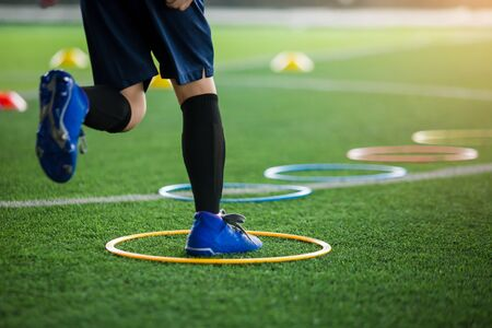 Photo pour selective focus to kid soccer player Jogging and jump at ring ladder marker on green artificial turf. equipment for training class of football academy. - image libre de droit