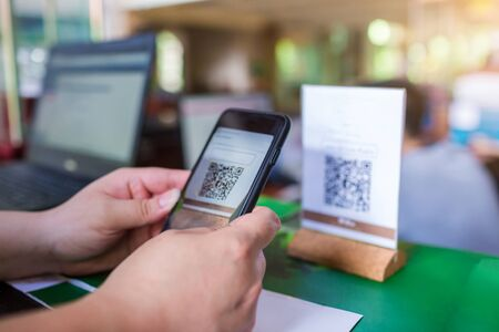 Photo pour Closeup of a hand holding phone and scanning QR code with blurry cashier at counter service. Man hands paying with QR code. Customer hands making payment through smart phone and scan code. - image libre de droit
