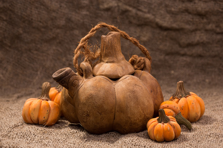 Kettle in the form of a pumpkin on a background of burlap