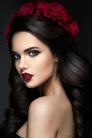 Photo pour Beauty Fashion Model Girl Portrait with Red Roses Hairstyle. Red Lips. Beautiful Luxury Makeup and Hair - image libre de droit