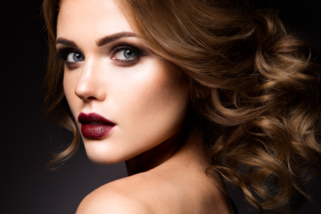 Photo pour Close-up portrait of beautiful woman with bright make-up and dark red lips - image libre de droit