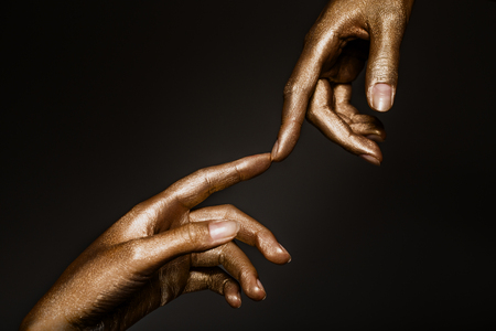 Photo for beautiful man's hands in golden paint on black background close up - Royalty Free Image