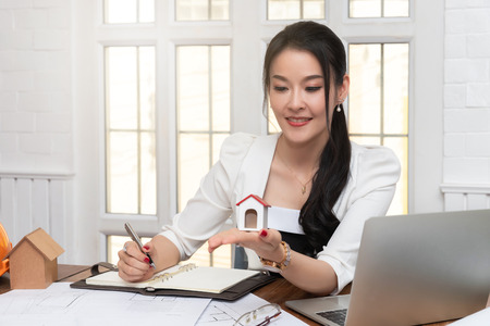 Foto de Business, architecture, building construction and real estate concept. Female real estate agent presenting a house model. Young female architect holding model of house in office. - Imagen libre de derechos