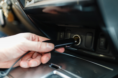 Foto für A man connects the device to the cigarette lighter of the car. The man's hand is plugging the car camera or phone adapter into the cigarette lighter into the car. - Lizenzfreies Bild