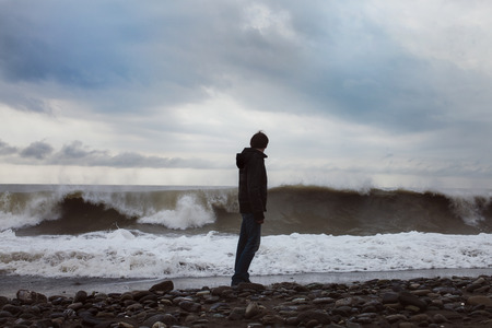 Foto de A young man standing on the sea shore - Imagen libre de derechos
