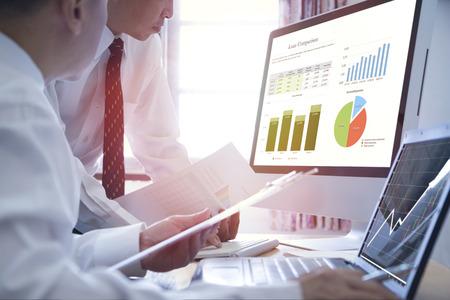 Foto de Two Asian Businessmen analysing on business loan comparison on desktop and notebook computer with colorful pie and bar graphs. - Imagen libre de derechos