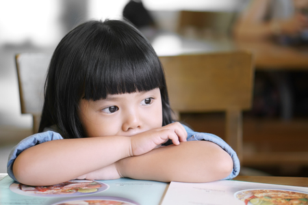 Foto de Asian children cute or kid girl lonely and sad with tears in the eye on food table because miss mom and dad or parents do not care with thinking something - Imagen libre de derechos