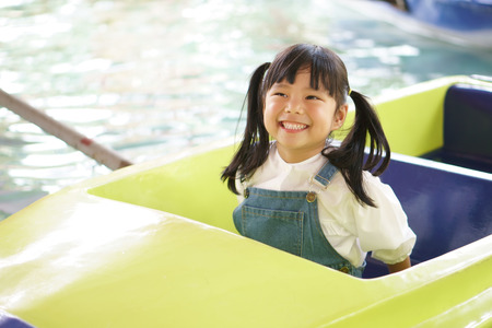 Photo for Asian children cute or kid girl enjoy smile and happy fun with boat ride on water or pool in amusement park on summer holiday relax and family vacation - Royalty Free Image