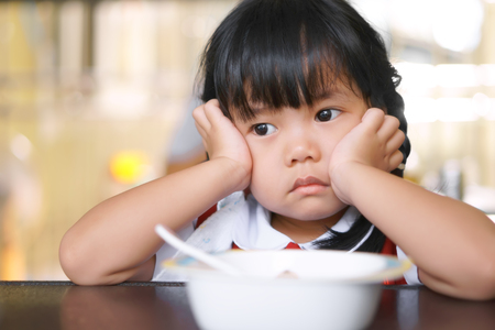 Foto de Asian children cute or kid girl student anorexia or sad with vacant and prop up or hand to cheek on food table for breakfast before going to school for study - Imagen libre de derechos
