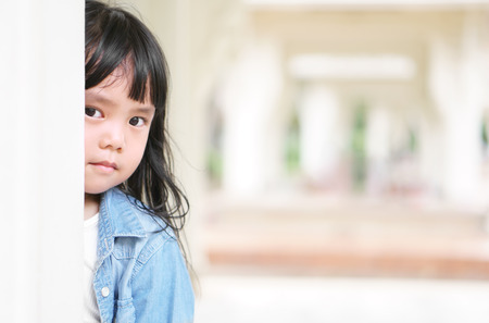 Photo for Asian children cute or kid girl peek with sneaks behind the pole and wear jeans for fashion with make face scowl and sad or angry at pavilion garden on holiday with space - Royalty Free Image