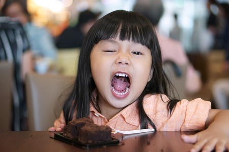 Photo for Asian children cute or kid girl enjoy and fun with happy eating delicious brownie chocolate cake for sweet dessert or snack on wood table and open mouth at lunch in restaurant or cafe for background - Royalty Free Image