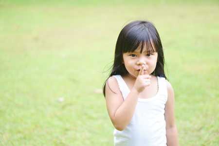 Photo for Asian children cute or kid girl squat and forefinger close mouth for tell quietly with silent and surprise or play hide and seek with green grass meadow space - Royalty Free Image
