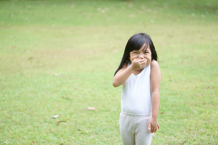Foto de Asian children cute or kid girl stand smile with laugh and hand close mouth for happy fun with enjoy or gag and secrets on green grass meadow space with wear white vest - Imagen libre de derechos