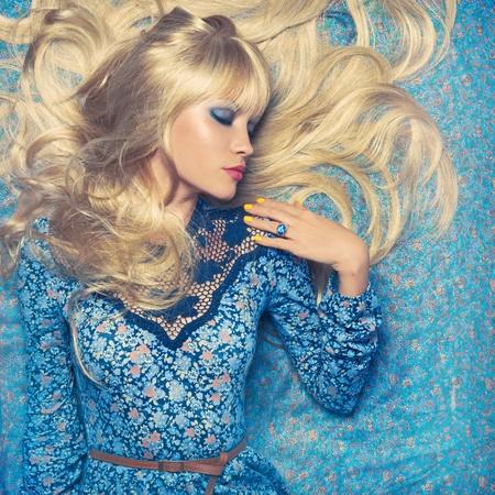 Beautiful sensual blonde lying on a blue pattern