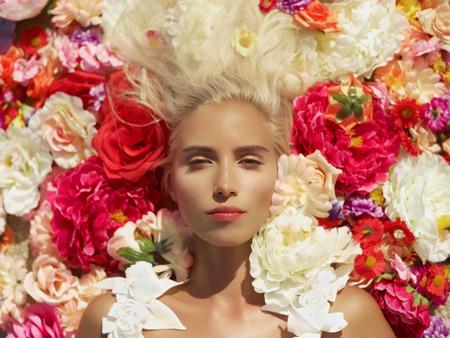 Photo pour Beautiful blonde young woman lying in flowers - image libre de droit