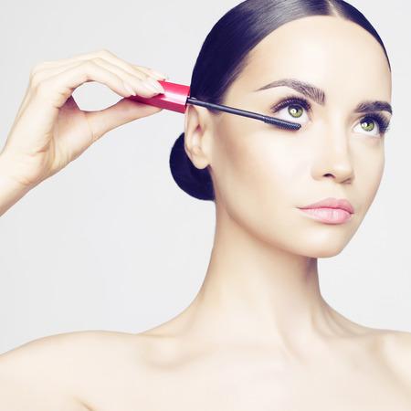 Foto de Studio fashion photo of beautiful young lady applied mascara.  Beauty and care. Extension eyelashes. Spa salon. Perfect face makeup - Imagen libre de derechos