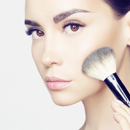 Foto de Studio fashion photo of beautiful young lady applying blush. - Imagen libre de derechos