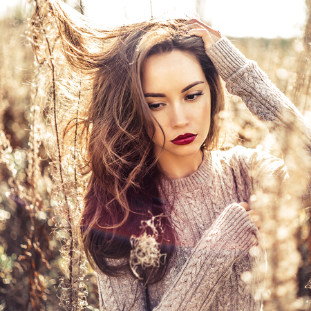 Photo pour Outdoor fashion photo of young beautiful lady in autumn landscape with dry flowers - image libre de droit