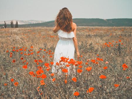 Foto de Outdoor photo of beautiful young woman in the poppy field - Imagen libre de derechos