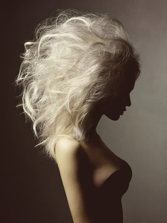 Photo for Fashion studio portrait of beautiful blonde woman with volume hairstyle on black background - Royalty Free Image