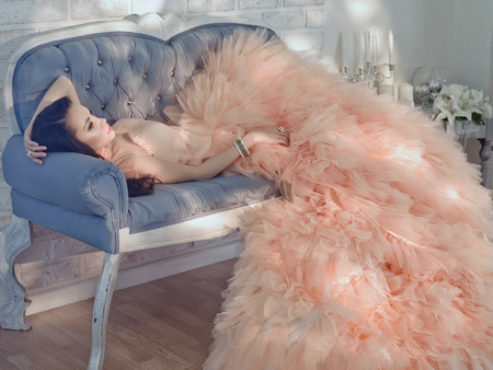 Photo pour Fashionable portrait of beautiful lady in gorgeous couture dress on sofa - image libre de droit