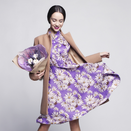 Photo pour Fashion studio photo of young stylish woman. Beige coat, lilac dress, bouquet of lavender. Catalogue clothes and accessories. Lookbook - image libre de droit