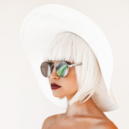 Foto de Outdoor fashion photo of young beautiful lady in white hat and mirror sunglasses. Summer Beach travel. Summer vibes - Imagen libre de derechos