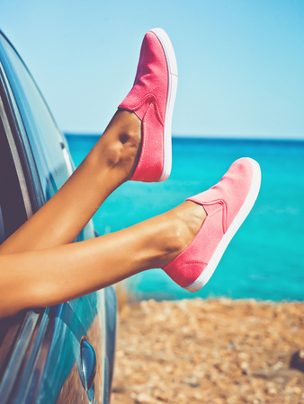 Foto de Outdoor photo of female legs from the window of car. Freedom, summer travel and road trip - Imagen libre de derechos